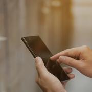Vendedor segurando um smartphone enquanto acessa informações